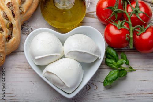 Foto auf Gartenposter Buffel Love mozzerella, balls of buffalo mozzarella, soft Italian scheese made from the milk of Italian Mediterranean buffalo in heart shaped plate