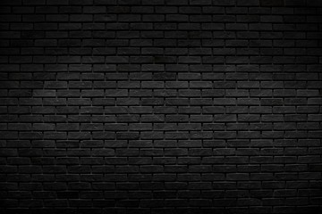 The old vintage black bricks wall with lighting decoration in dark tone style on architecture and background design concept