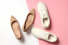 White Sneakers And High Heel Shoes On A Colored Background Top View. Women's Shoes. Classic And Sport Shoes.
