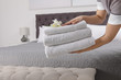 Maid holding fresh towels with flowers in hotel room, closeup