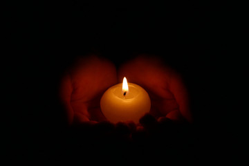 Hands holding a burning candle in dark. Burning candle in the children's hands on a dark background.