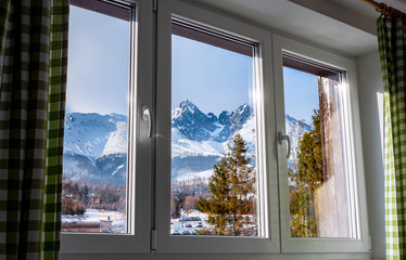 Piękny widok przez okno na Tatry z hotelu w Tatrzańskiej Łomnicy na Słowacji w sezonie zimowym.