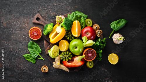 Fototapeta Food containing vitamin C: Orange, lemon, apple, rose, garlic, broccoli, apple, kiwi, spinach. Top view. On a brown background. obraz