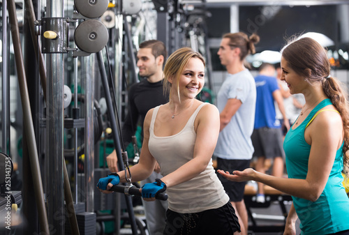 Fotografiet  Adults having strength training under coach control in gym