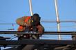 Welder working on scaffolding. Construction worker against the blue sky background, welding works