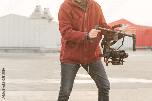 Photo Close up photo of man of a videographer, holds in the hands of a stabilizer and EVIL camera