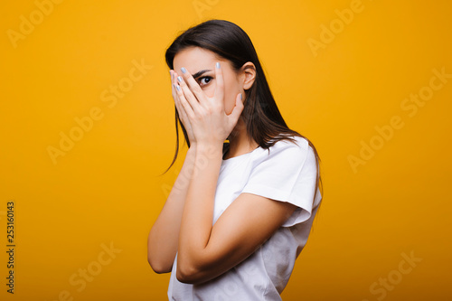 Photo  Pretty young caucasian female dressed in white shirt looking through the hand surprised of what she is seeing against yellow background