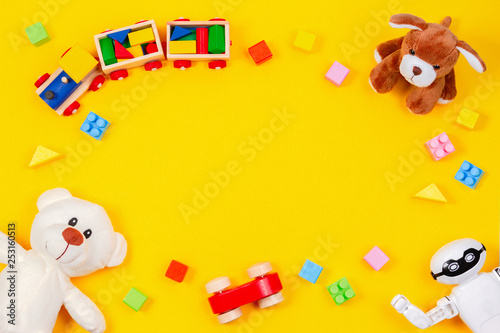 Obraz Kids toys background. White teddy bear, wooden train, toy car, robot, colorful blocks on yellow background - fototapety do salonu