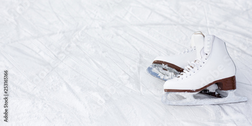 white figure skates and copy space over ice background with marks from skating