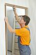 Door frame installation. Carpenter works with drill