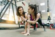 Two young healthy women exercising together in gym. Fitness, sport, training, people, healthy lifestyle concept.
