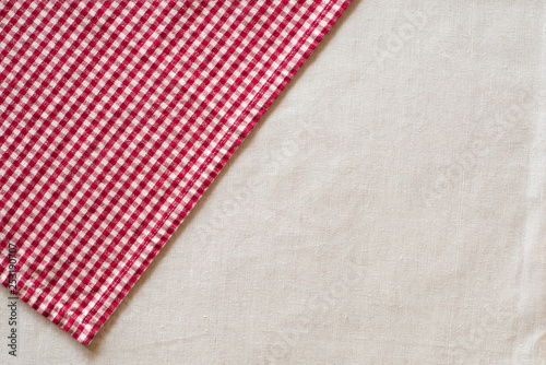 Red and White Checked Cloth at angle on upper corner of off white or cream colored linen table cloth.  Horizontal above view with room or space for copy, text or your words or design