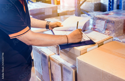 Cuadros en Lienzo Warehouse worker writing on clipboard with checklist details shipments boxes, Warehouse inventory managemant