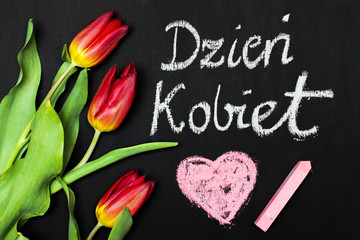 FototapetaWomen's Day card and a bouquet of beautiful tulips on blackboard background, with Polish words