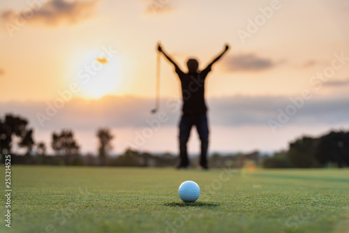 Foto Silhouette golfer showing happiness when win in game , white golf ball on green grass of golf course with blur background