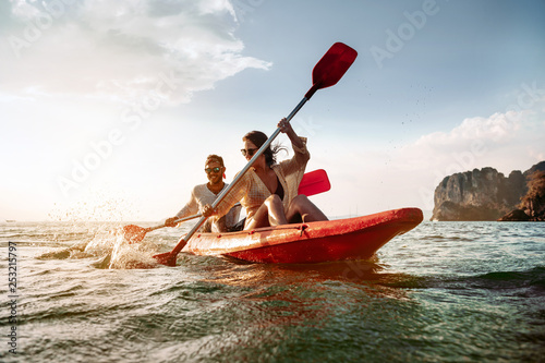 Foto Happy couple walks by sea kayak or canoe