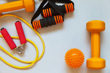 Set Of Equipment For Physical Exercise: Dumbbells, Rubber Chest Expanders, Hand Flexor And Massage Ball On Light Background. Active Healthy Lifestyle. Top View, Flat Lay