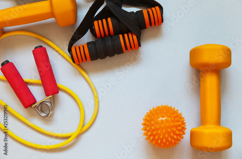 Fototapeta Set of equipment for physical exercise: dumbbells, rubber chest expanders, hand flexor and massage ball on light background. Active healthy lifestyle. Top view, flat lay obraz