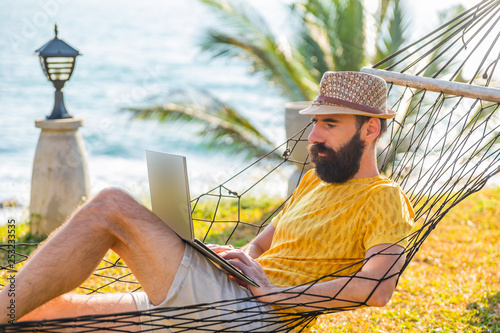 Valokuvatapetti Man working with a laptop, on a hammock in the beach.