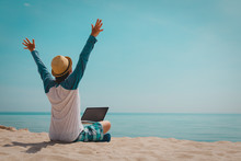 Happy Young Man Working On Laptop At Beach