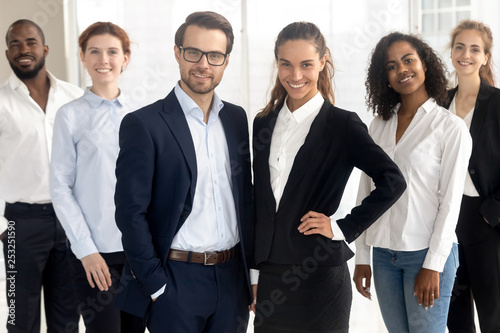 Smiling diverse office workers group posing looking at camera