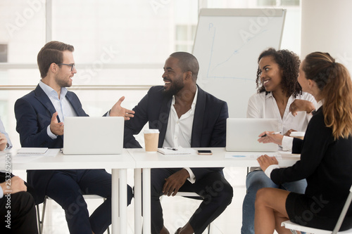 Fotografija  Multiracial employees sitting at boardroom desk listening team leader