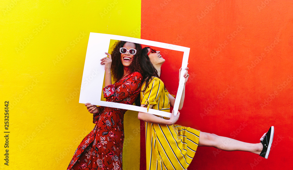 Fototapeta Smiling women with empty photo frame