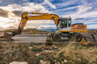 Excavator machine carrying out road maintenance works