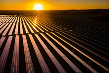 Aerial Looking Over A Modern Solar Farm At Sunrise In The English Countryside