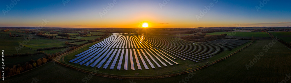Fototapety, obrazy: Aerial looking over a modern solar farm at sunrise in the English countryside panoramic
