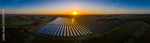 Aerial looking over a modern solar farm at sunrise in the English countryside panoramic