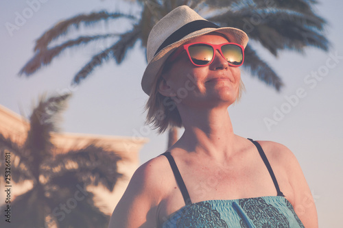 Fotografie, Obraz  Woman on a holiday with pink sunglasses and white hat relaxing outdoor on a beau