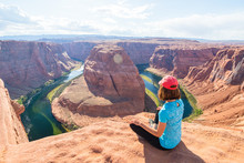 Enjoying The View At The Incredible Horseshoe Bend, A Horseshoe-shaped Meander Of The Colorado River Located Near The Town Of Page, Arizona. Young Woman Enjoying View Of Horseshoe Bend, Arizona.