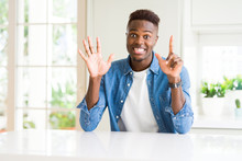 Handsome African American Man At Home Showing And Pointing Up With Fingers Number Seven While Smiling Confident And Happy.