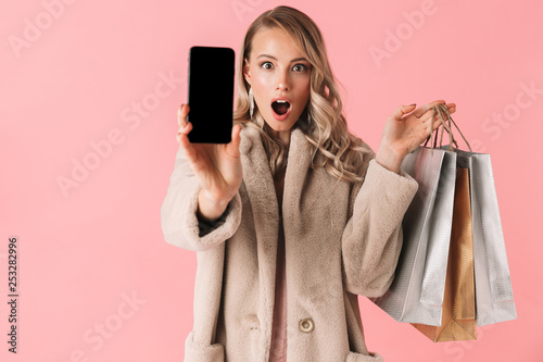 Beautiful young pretty woman posing isolated over pink wall background showing display of mobile phone.