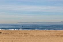 Looking Out To Sea From Huntington Beach On The Californian Coast, With Paddle Boarders On The Water