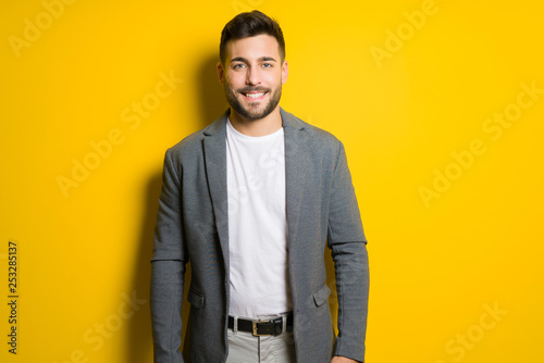 Fotografia  Young handsome man possing and modeling over yellow isolated background
