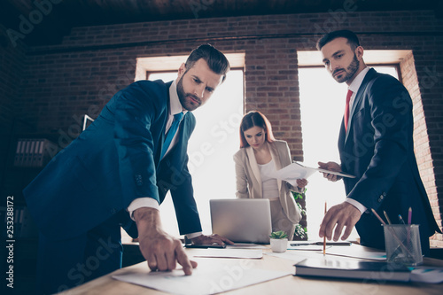 Close up photo three career partners she her business lady he him his guys look charts discuss new project check income thoughtful ponder pensive busy stand office table wearing formal wear suit