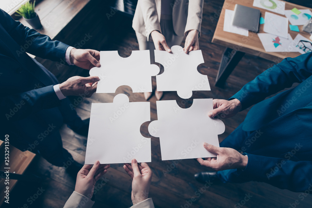 Fototapeta Cropped top above high angle view of stylish elegant sharks holding in hands fitting big large puzzle pieces together team building in loft industrial interior work place station