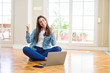 Beautiful young woman sitting on the floor with crossed legs using laptop very happy and excited doing winner gesture with arms raised, smiling and screaming for success. Celebration concept.