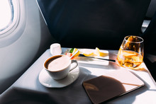 Passenger Table In Airplane With Drinks, Snacks And Digital Tablet With Blank Screen