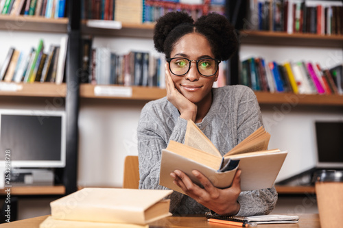Canvas Print Happy young student girl studying at the library