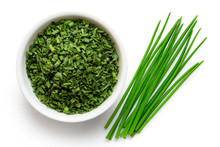 Dried Chopped Chives In White Ceramic Bowl Next To A Pile Of Whole Fresh Chives Isolated On White From Above.