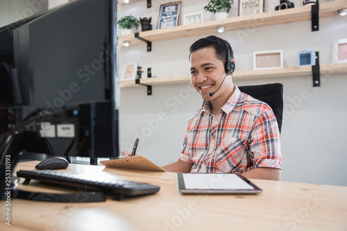 Fotografija asian tele marketing on duty talk via phone to his customer in the office