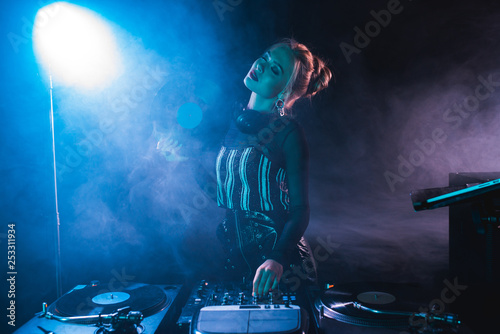 blonde dj woman standing with closed eyes near dj equipment and holding retro vinyl record in nightclub with smoke - 253311934