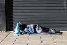 Homeless Person Asleep In A Sleeping Bag On A Pavement Sidewalk In Front Of A Metal Shutter.  Face Not Visable.