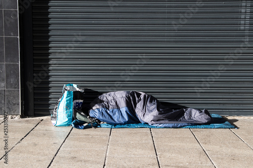 Homeless person asleep in a sleeping bag on a pavement sidewalk in front of a metal shutter Canvas-taulu