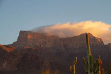 Morning Image Of The Superstition Mountains Of Arizona With A Cloud Over The Peaks Reflecting The Morning Light.