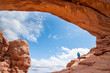 Young woman is standing under the North Window arch in Arches National Park in Utah. Female tourist is standing under a natural arch in Arches National Park. Travel and adventure concept.
