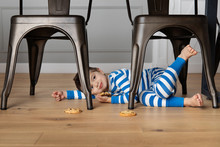 Young Child Hiding Under Kitchen Table Holding Cookie